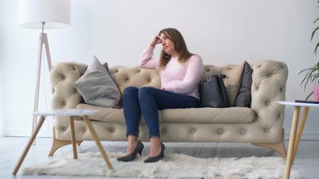 vulnerability : Depressed businesswoman in trendy clothes and high heels sitting on the sofa at home and looking away with stare full of sadness and despair. Sad beautiful female experiencing emotional stress. Stock Footage