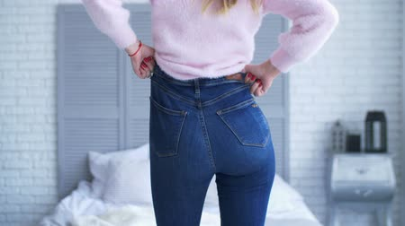 calças justas : Rear view of adult woman with perfect body and buttocks fitting in tight jeans in bedroom after gaining weight. Midsection of female hands unable to close the pants due to gaining fat on hips at home.
