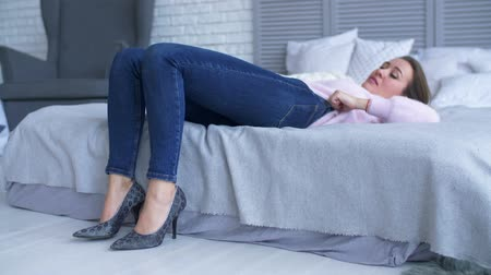 postel : Charming focused female in high heel shoes lying on her back on the bed, struggling to close her jeans in bedroom. Beautiful woman trying to squeeze into too tight pants whily lying on the bed at home