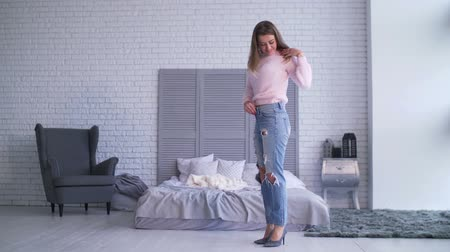 roztrhaný : Excited adult woman in loose old jeans showing success of weight loss program while standing in her bedroom. Positive female in baggy ragged denim happy to see how much weight she lost at home.