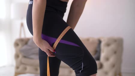 measure tape : Midsection of fitness woman in leggings measuring her slim thigh with measuring tape over domestic room background. Closeup of female hands with measuring tape checking her legs size after workout. Stock Footage