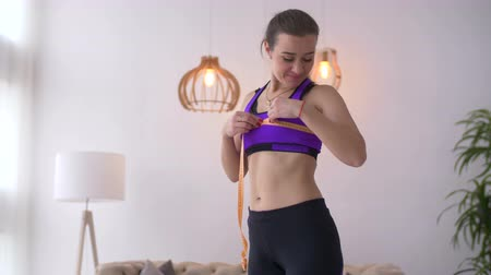 болваны : Sporty lovely fit woman measuring her breast size with tape measure while standing in domestic room. Beautiful fitness female insportswear checking her breast measurement with measuring tape.