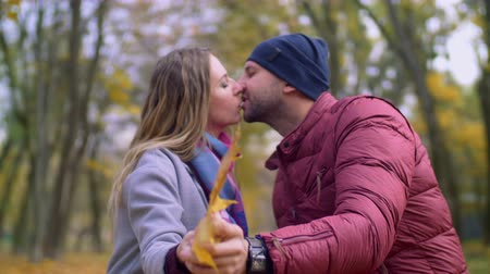 sentimentální : Portrait of attractive couple in love tenderly kissing, expressing love and happiness during romantic date on autumn day. Couple in passionate kiss hiding behind yellow maple leaf in fall season. Dostupné videozáznamy