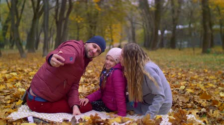 dişlek gülümseme : Joyful parents and smiling daughter taking selfie photo on smart phone in autumn park while sitting on picnic blanket. Happy family making self portrait with cellphone while relaxing in autumn nature.