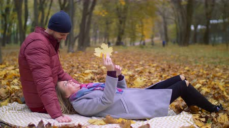 líbání : Affectionate couple in love cherishing every moments together and bonding while relaxing on picnic blanket in autumn nature. Chatting couple enjoying leisure on romantic day in indian summer.