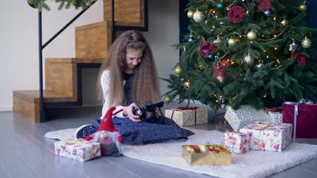picture box : Cheerful preadolescent girl viewing photos on digital camera while sitting under the christmas tree, surrounded by gift boxes. Smiling cute child looking through pictures on photo camera at xmas.