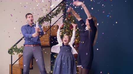 fete : Joyful excited family with daughter blowing-up christmas firecracker while celebrating christmas in festive decorated room. Ecstatic family celebrating xmas with multi colored confetti fallen over. Stock Footage