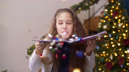ciltli : Portrait of adorable preadolescent girl blowing multi colored glitter confetti from open hardcover book over christmas decorated room background. Beautiful child having fun with shiny confetti at xmas