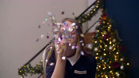 rejoice : Portrait of beautiful adult woman with eyes closed blowing colorful confetti from her hand and smiling over christmas tree background. Positive female blowing glitters from her palms during christmas.