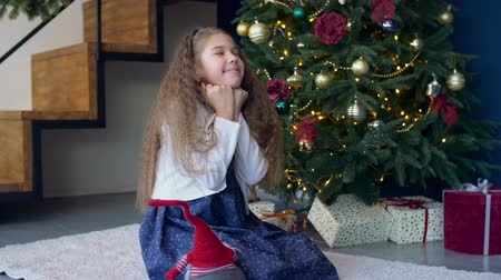 święta : Positive joyful little girl with eyes closed tightly, propped her head on clenched fists making a wish, asking Santa Claus to fulfill dreams at christmas time over festive decorated room background. Wideo