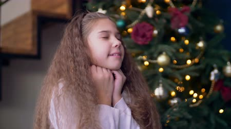 święta : Portrait of cheerful elementary age girl making a wish with eyes closed ,propped head on fist near christmas tree at home. Closeup of adorable child asking Santa Claus to fulfill dreams at Christmas. Wideo