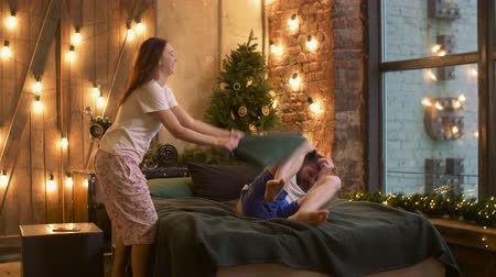 bochechudo : Joyful playful woman and bearded handsome man in pajamas having fun on bed and playing pillow fight while enjoying the company of each other in hotel room during winter holidays.