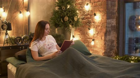 ciltli : Beautiful smiling woman in pajamas enjoying pastime in her bed, reading a book in domestic room at night. Cheerful pretty long brown hair female relaxing with book in illuminated bedroom.