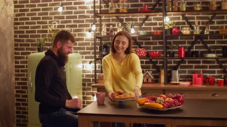 croissants : Happy smiling woman serving coffee and croissants on kitchen table while attractive couple having snack together after work in the evening. Loving couple enjoying time together in domestic kitchen. Stock Footage