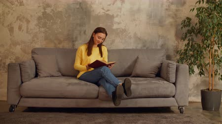 ciltli : Cheerful intelligent young woman in casual outfit enjoying her pastime while sitting comfortably on sofa after work. Beautiful female reading hardcover book while relaxing on the couch in the evening.