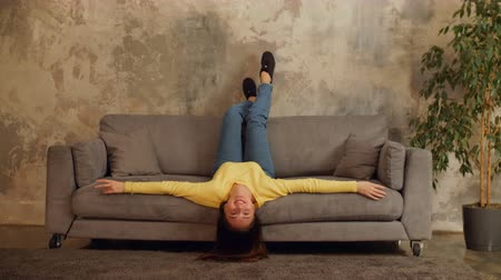 looking down : Beautiful carefree woman lying on sofa with head upside down in loft apartment. Cheerful young female enjoying leisure, resting on the couch with head upside down in domestic room in the evening. Stock Footage