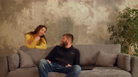 bewilderment : Smiling attractive woman caught her bearded boyfriend watching some embarrassing content online on laptop while sitting on sofa. Ironic girl caught man browsing naughty content via laptop pc at home.
