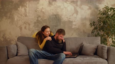 avoiding : Workaholic bearded man busy working laptop pc, ignoring pretty girlfriend embracing him from behind while sitting on sofa at home. Woman feeling sadly and lonely, not having attention from boyfriend.