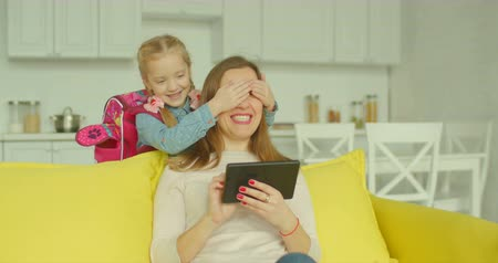 coming home : Beautiful mother sitting on sofa, browsing social media content on tablet pc and her adorable schoolgirl with backpack covering her eyes with palms to make surprise after coming home from school. Stock Footage