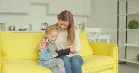 pozitivity : Charming smiling mother and cute elementary age daughter sitting on sofa in lounge, networking with digital tablet. Positive parent and adorable little girl browsing online with tablet pc at home.