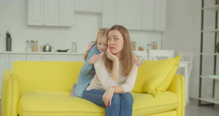 compreensão : Affectionate little daughter embracing sad depressed mother with love and support while sitting on sofa in domestic interior. Caring little girl comforting unhappy mom, hugging from behind at home.