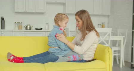 понимание : Caring affectionate mother comforting her upset adorable daughter while sitting face to face on cozy sofa in domestic room. Loving single mom consoling sad pensive elementary age girl at home.