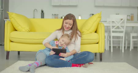 öğrenme : Carefree attractive mother and relaxed adorable little daughter playing online game using digital tablet in loft apartment. Positive cheerful family with tablet pc enjoying freetime during weekend.