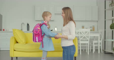 anne : Caring mother preparing and cheering up cute little daughter with backpack before first day of school in domestic room. Affectionate mum kissing goodbye schoolgirl as she leaves for primary school.