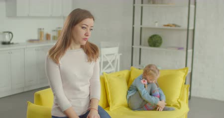 adversidade : Sad worried beautiful mother having quarrel with her cute elementary age daughter in domestic room. Cute little girl throwing pillow into her upset pensive mum after conflict at home. Stock Footage