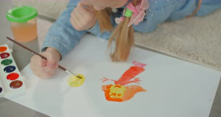 гуашь : Close-up of childs hands with paintbrush creating picture with colorful paints while lying on floor in domestic room. Little girl painting with watercolors while enjoying leisure after school at home Стоковые видеозаписи