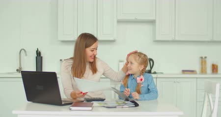 recibo : Positive cheerful mother with laptop and calculator calculating bills, working with financial documents and planning family budget while cute little daughter sitting next to her mum in modern kitchen.
