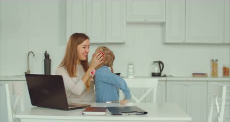 anne : Affectionate caring single mother working laptop, embracing and kissing her cute little daughter with love and happiness in domestic kitchen. Loving freelance mum always has time for her child. Stok Video