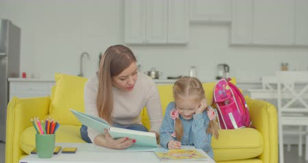 disinterest : Caring mother with textbook teaching her lazy schoolgirl busy with drawing and distracting from homework for elementary school. Carefree cute daughter ignoring help of her mom with studying at home.