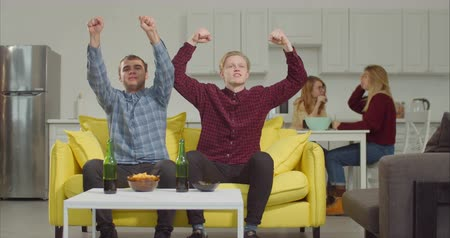 raising fist : Two excited male friends celebrating a goal, raising clenched fists and screaming happily while watchng soccer game on tv in domestic room. Excited football fans emotionally watching match at home. Stock Footage