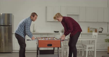 engrossed : Cheerful excited best male frineds playing table football while enjoying freetime together in loft apartment. Positive roommates having fun and relaxing playing table soccer after work at home. Stock Footage