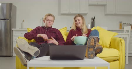 watch tv : Relaxed young couple sitting on sofa with legs on coffee table, eating snack and enjoying online tv on laptop while resting in domestic room. Cheerful friends watching movie online on computer at home Stock Footage