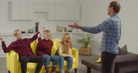 engrossed : Cheerful man acting out a word in the game of charades, gesturing and showing pantomime to engrossed diverse teenage friends at home. Smart friends guessing word in charades while relaxing indoors. Stock Footage