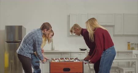 futball : Cheerful joyful young couple defeating opponets in foosball game and celebrating the win with high five while relaxing together at home. Positive teenagers enjoying leisure playing table soccer.