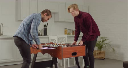 engrossed : Excited cheerful male friends enjoying freetime playing table football in loft apartment. Positive roommates having fun, playing foosball while spending leisure together at home after work.