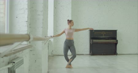 nőiesség : Elegant classic ballet dancer in sporty clothes rehearsing in ballet class. Beautiful ballerina with perfect body performing choreographic exercises, doing dedans at ballet barre in dance studio. Stock mozgókép