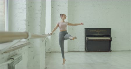 kadınlık : Elegant classic ballet dancer in sporty clothes rehearsing in ballet class. Ballerina with perfect body performing choreographic exercises, doing battement frapper at ballet barre in dance studio