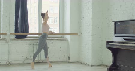 гибкий : Elegant ballet dancer in sport cloches practicing degage choreographic exercises at barre in rehearsal room. Graceful ballerrina performing classic dance moves during training in ballet studio.