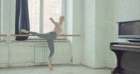 стенд : Elegant ballet dancer in sport cloches practicing relevelent choreographic exercises at barre in rehearsal room. Graceful ballerrina performing classic dance moves during training in ballet studio.