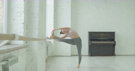 sznurek : Pretty graceful dancer in sportswear stretching leg and spine muscles at barre before rehearsal. Elegant ballet dancer warming up in dance studio with stretches before practicing dance or exercises.