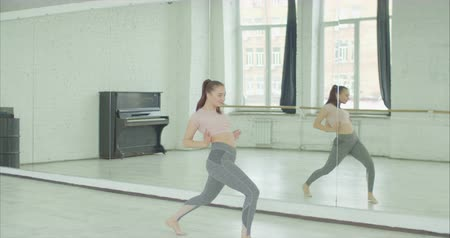 engrossed : Elegant slim female dancer with ponytail in sportswear rehearsing dance against mirror in dance studio. Emotional fully engrossed in dance woman unleashing her creativity in contemporary dance.