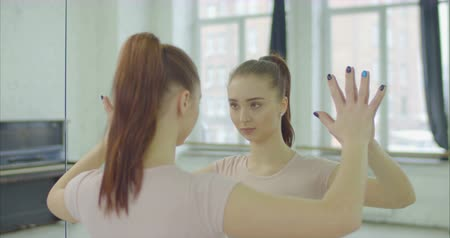 dançarina : Serious attractive woman with ponytail touching mirror, looking at her reflection with concentration and determination. Focused self confident young female leaning against a big mirror in dance studio Stock Footage
