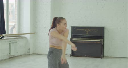 гибкий : Elegant attractive female dancer improvising contemporary style dance while rehearsing in dance studio. Cheerful creative woman performing smooth graceful dance moves during training class indoors.