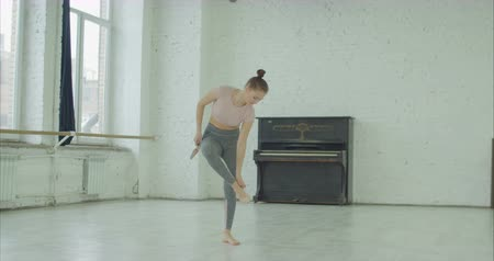 sinir : Upset graceful female dancer disappointed by going off the beat of dance, taking off and throwing away pointe in despair while rehearshing contemporary style dance in studio.