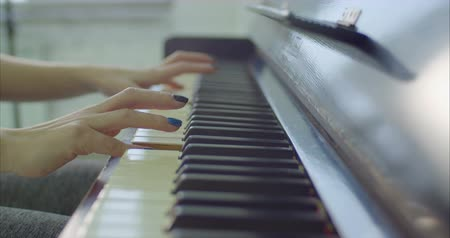 piano parts : Close-up female musician hands with colorful manicured nails playing on piano keyboard during rehearsal. Artistic woman enjoying classical music while playing on piano.