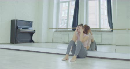 leunen : Crying upset female dancer leaning on mirror and sliding down to floor in dance studio after imperfect rehearsal. Attractive woman in tears sitting on the floor against big mirror in rehearsal room.